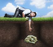 picture of rich soil  - Businessman trying to get treasure in the soil - JPG