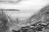 picture of wall-stone  - stone wall shelter on a beautiful beach at the maharees county Kerry Ireland in black and white - JPG