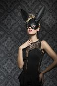 picture of fancy-dress  - Sexy pretty elegant blonde woman in black dress and rabbit mask with dark make up - JPG