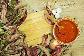 image of pepper  - Wooden spoon of cayenne pepper in bowl with cayenne pepper on wooden table - JPG