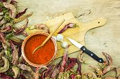 picture of pepper  - Wooden spoon of cayenne pepper in bowl with cayenne pepper on wooden table - JPG