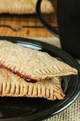 stock photo of fill  - Whole wheat toaster pastries lightly dusted with sugar crystals and filled with raspberry filling - JPG
