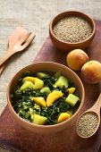 stock photo of peach  - Bowl of spinach peach and potato curry dish with sesame seeds and peaches in the back photographed with natural light  - JPG