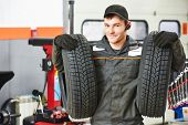 stock photo of assemblage  - repairman mechanic portrait in car auto repair or maintenance shop service station with automobile wheel tire - JPG