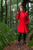 foto of overcoats  - Young woman feeling sad walking on a forest wearing a red overcoat during winter under a sunlight ray - JPG