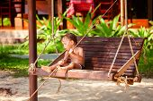stock photo of swing  - boy on a swing at the beach - JPG