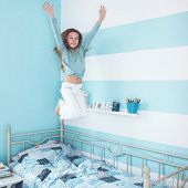 pic of fidget  - 8 years old kid girl jumping on the bed at her room - JPG