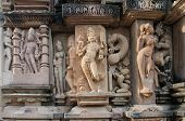 stock photo of hindu  - Stone carved erotic bas relief in Hindu temple in Khajuraho - JPG