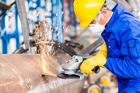 foto of abrasion  - Industrial worker in manufacturing plant grinding to finish a pipeline - JPG