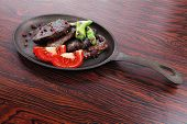 image of peppercorns  - fresh roast beef fillet mignon on old retro style cast iron pan on retro wooden table as background with rosemary peppercorn and tomatoes - JPG