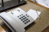 foto of dial pad  - Telephone for customer service and blank white note paper with pen in hotel room - JPG