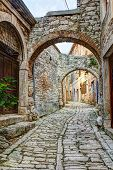 stock photo of stone house  - A typical narrow street or alley with stone houses in the town of Bale or Valle in Istria Croatia situated on a hilltop - JPG