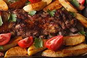 foto of baby back ribs  - Grilled pork ribs potatoes and tomatoes macro - JPG