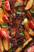 image of baby back ribs  - Grilled pork ribs potatoes and tomatoes macro - JPG