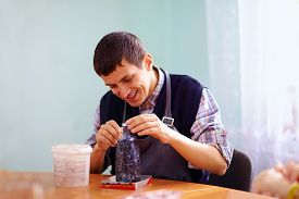 stock photo of daycare  - young adult man with disability engaged in craftsmanship on practical lesson in rehabilitation center - JPG