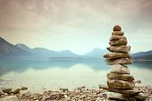 Balanced Stone Pyramide On Shore, Blue Water Of Mountain Lake. poster