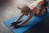 Woman On Fitness Mat Doing Stretching Workout At Gym. poster