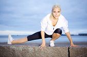 pic of hamstring  - Beautiful woman doing stretching exercise on beach - JPG