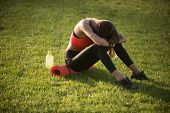 Tired Woman In Sportswear Relax After Workout, Training. Sportswoman Sit On Green Grass With Gym Equ poster
