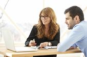 Executive Businesswoman Giving Advice To Young Professional Man poster