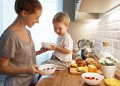 Preparation Of A Family Breakfast. Mother And Baby Son Cook Porridge In Morning poster