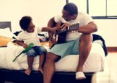 Black father enjoy playing guitar with his child together happiness poster