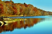 stock photo of dock a pond  - Lone fisherman casts his line into small lake in northern Arkansas - JPG