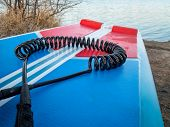 coil safety leash on a deck of stand up paddleboard - safety equipment poster