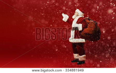 poster of Full length portrait of the good old Santa Claus with a bag of gifts under a snowfall on a red backg