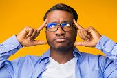 Creative Thinking. Thoughtful Black Man Concentrating Hard On An Idea Pointing Fingers At Forehead S poster