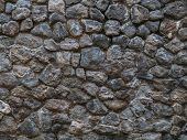Stone Wall - Building Feature. Background Image Of Weathered Stained Old Stone Wall Of Rough Stones  poster
