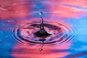 Single Water Drop At Top Of Splash. Vibrant Red And Blue Colors, High Speed Water Drop Photography poster