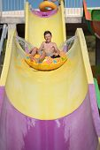 Boy Having Fun On The Water Slide On Floater In The Aqua Fun Park. He Is Enjoying His Summer Vacatio poster