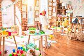Beautiful blonde toddler wearing fanny colorful propeller cap. Walking around lots of toys at kinder poster
