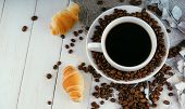 Cup Of Coffee With Coffee Beans And A Croissant On Vintage Wooden Table. Homemade Croissant Served W poster