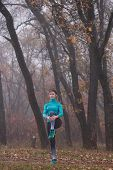 Fit Woman Athlete Doing Stretches Female Runner. Stretching Her Legs. Fallen Foliage On The Ground,  poster