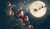 Merry Christmas and happy holidays! Cute little children with mom and dad. Santa Claus flying in his poster