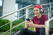 Young man listen to the music in a big earphones, in the street.  Happy teenage boy with mobile phon poster