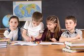 stock photo of teenage boys  - Four schoolchildren aged 11 at the desk in classroom - JPG
