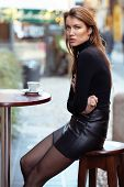 Young caucasian fashionable woman dressed in black clothes drinks coffee outdoor over Christmas Eve  poster