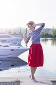 Beautiful Girl In A Straw Hat On The Pier Near The Sea Yachts And Boats. Girl In A Red Skirt And A S poster