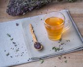 Warm Oregano Tea In A Glass Cup On Linen Beige Napkins On The Background Of Dry Oregano. A Wooden Sm poster