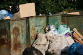 stock photo of dumpster  - Garbage dumpsters cardboard boxes and bags full of trash - JPG