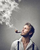 stock photo of tobacco-pipe  - handsome man smokes a pipe - JPG