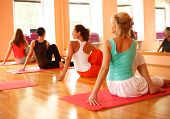stock photo of yoga instructor  - Women practicing yoga at health club with instructor - JPG