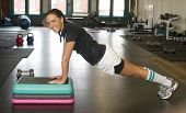 Woman In Gym Holds Plank Position During Boot Camp Session