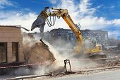 stock photo of power-shovel  - Bulldozer crushing the building at construction site - JPG