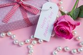 picture of mother-of-pearl  - Pink rose with gift and string of pearls and tag for mothers day on pink surface - JPG