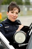 stock photo of lightbar  - a female police officer writes a ticket while standing next to her patrol car - JPG