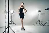 stock photo of flashing  - Beautiful female model posing at studio in the light flashes - JPG